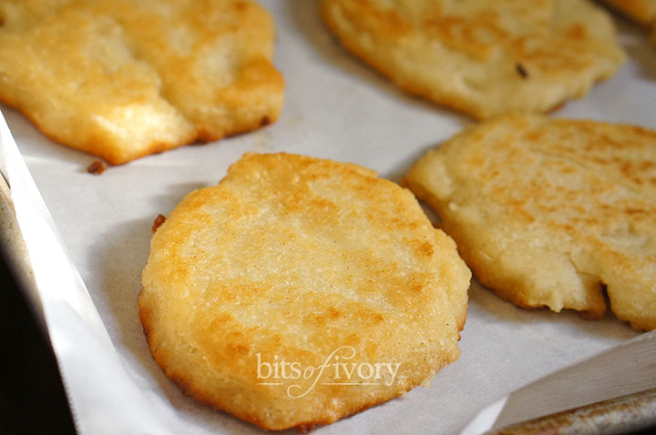 Fried arepas on a cookie sheet ready to bake