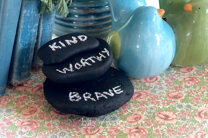Rocks painted with chalkboard paint with the words kind, worthy, and brave written on them