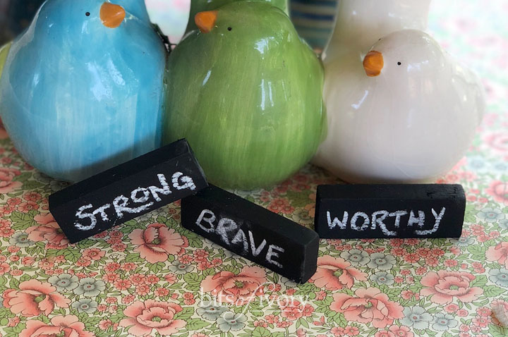 Upcycled game pieces create little chalkboards with strong, brave, and worthy written on them